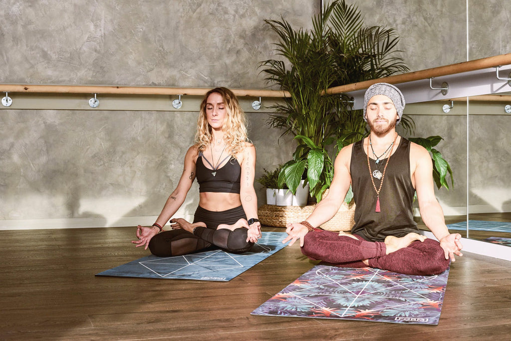 Man and woman doing yoga in a studio