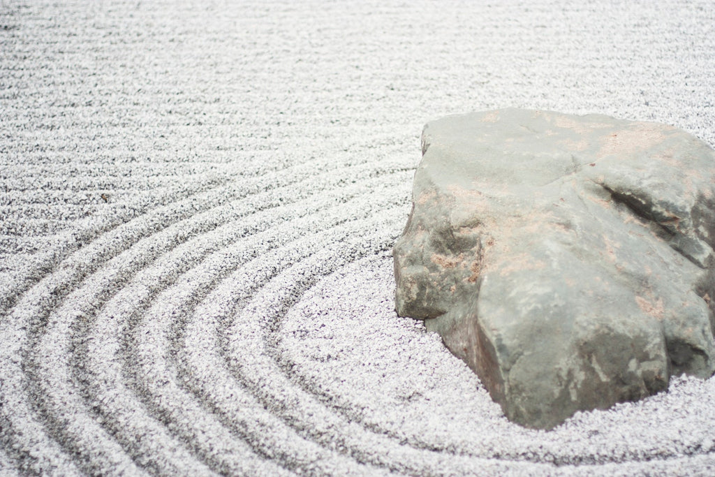 Rock in sand that has been raked with a pattern