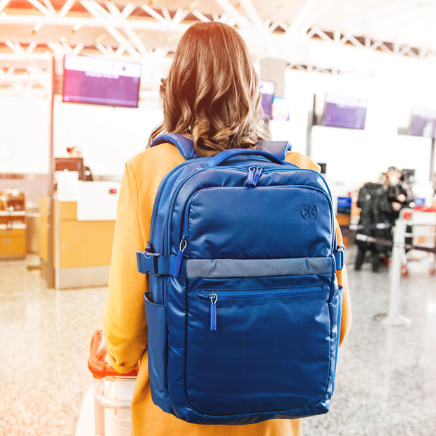 Woman walking through airport wearing her Speck Travel Business Backpack