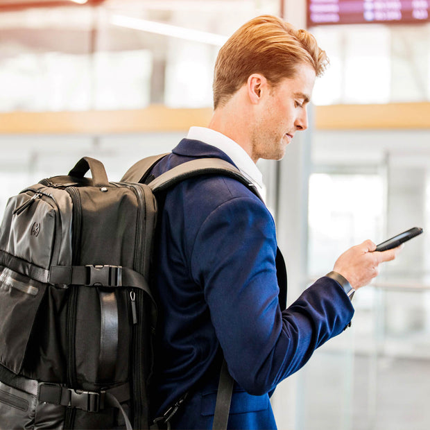 Man walking through airport looking at smartphone while wearing his Speck Travel Travel Backpack