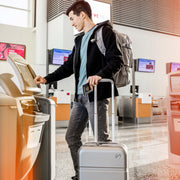 Man in an airport checking in with Speck Travel 22-inch Carry-On