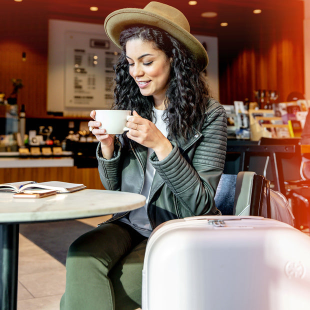 Woman sipping coffee in a cafe next to her Speck Travel 26-inch Upright