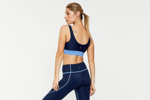 Femininely Regimented Pectoralis Navy and light blue bra top worn with Vastus mid rise full length navy legging with contrast stitching, back view