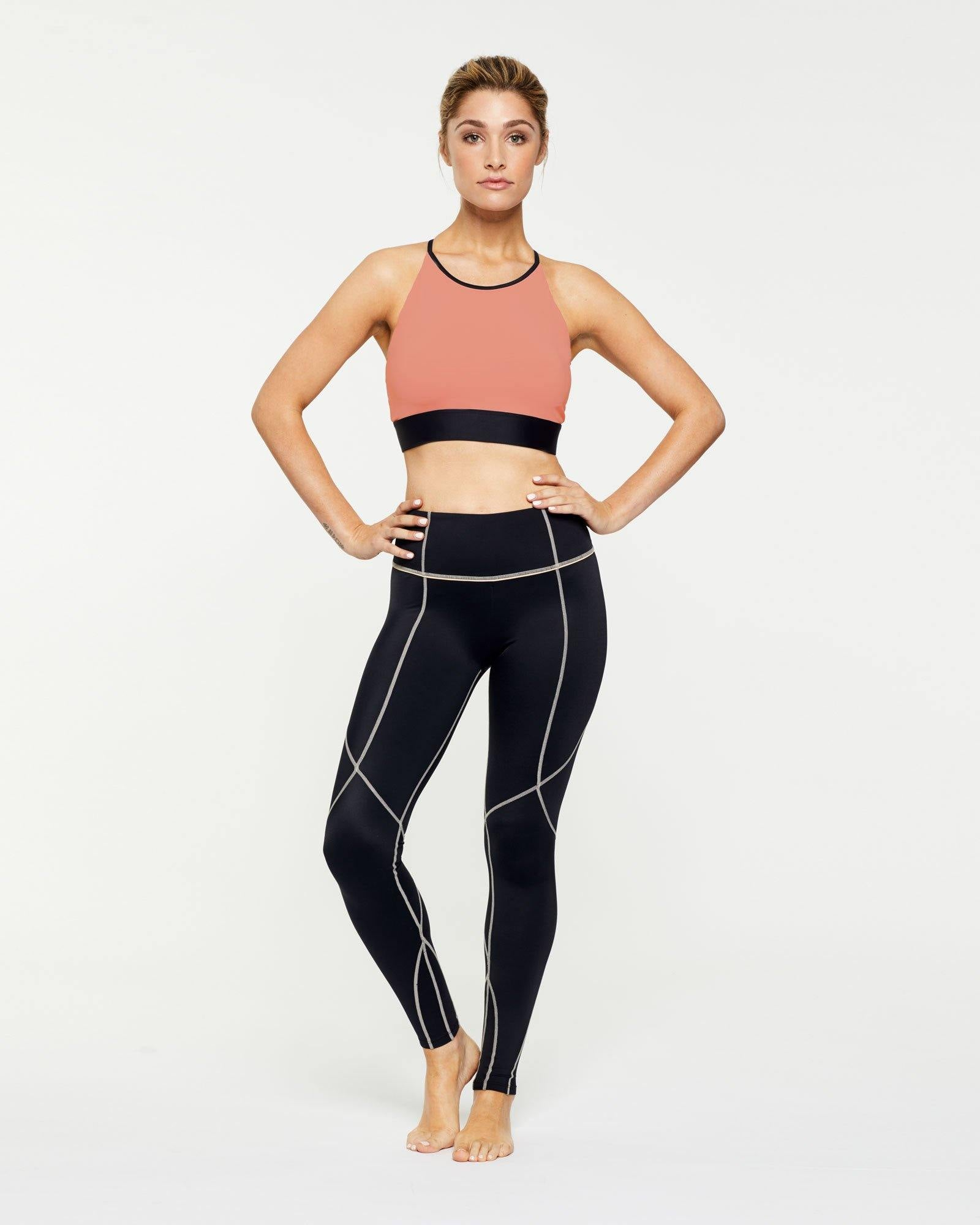 Warrior Trapezius Halter Crop Top peach with contrast black binding worn with Vastus mid waist full length legging, front view