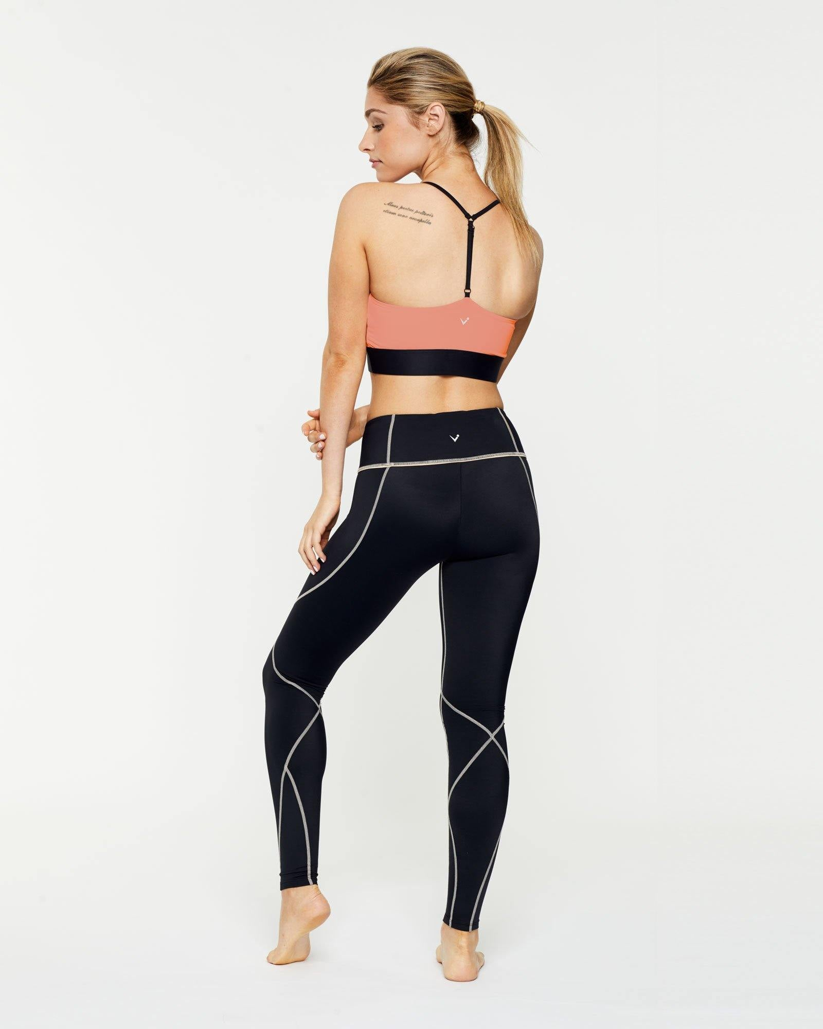 Trapezius Warrior Sophisticate peach crop top high neck finish with contrast black binding, halter back worn with Vastus mid waist full length legging, back view
