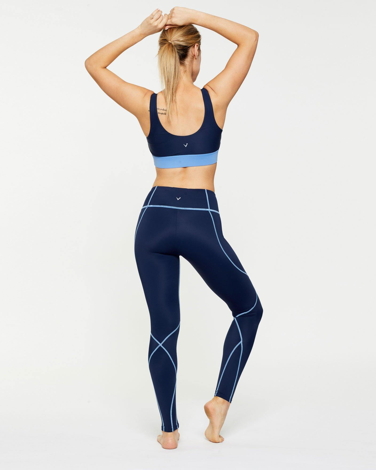 Femininely Pectoralis Navy bra top with contrast under bust band worn with Vastus navy mid waist long legging, back view, great for pilates, barre and in-studio workouts