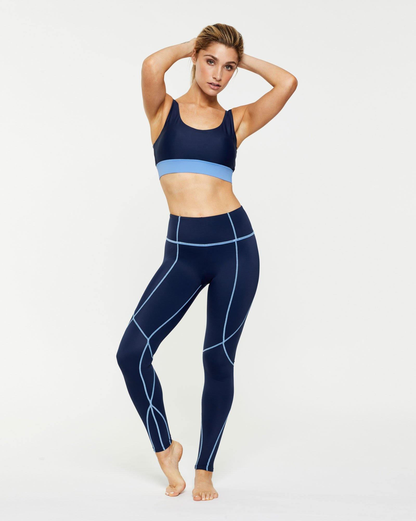 Femininely Vastus mid waist long Navy legging with contrast stitching, front view worn with Pectoralis active bra top, for pilates, barre, yoga, gym and studio workouts