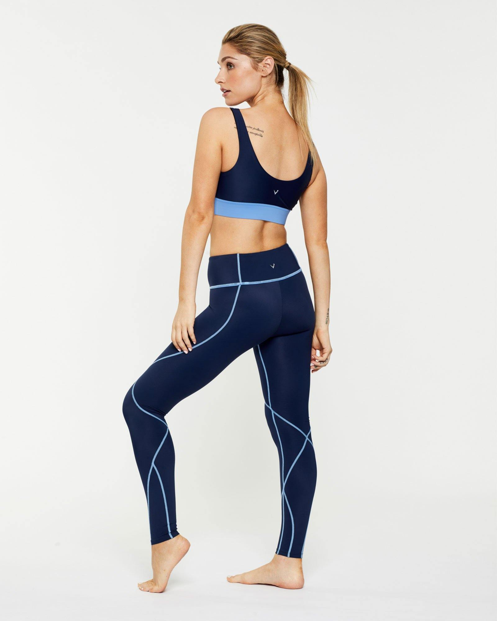 Femininely Vastus mid waist long Navy legging with contrast stitching, side view worn with Pectoralis active bra top, for pilates, barre, yoga, gym and studio workouts