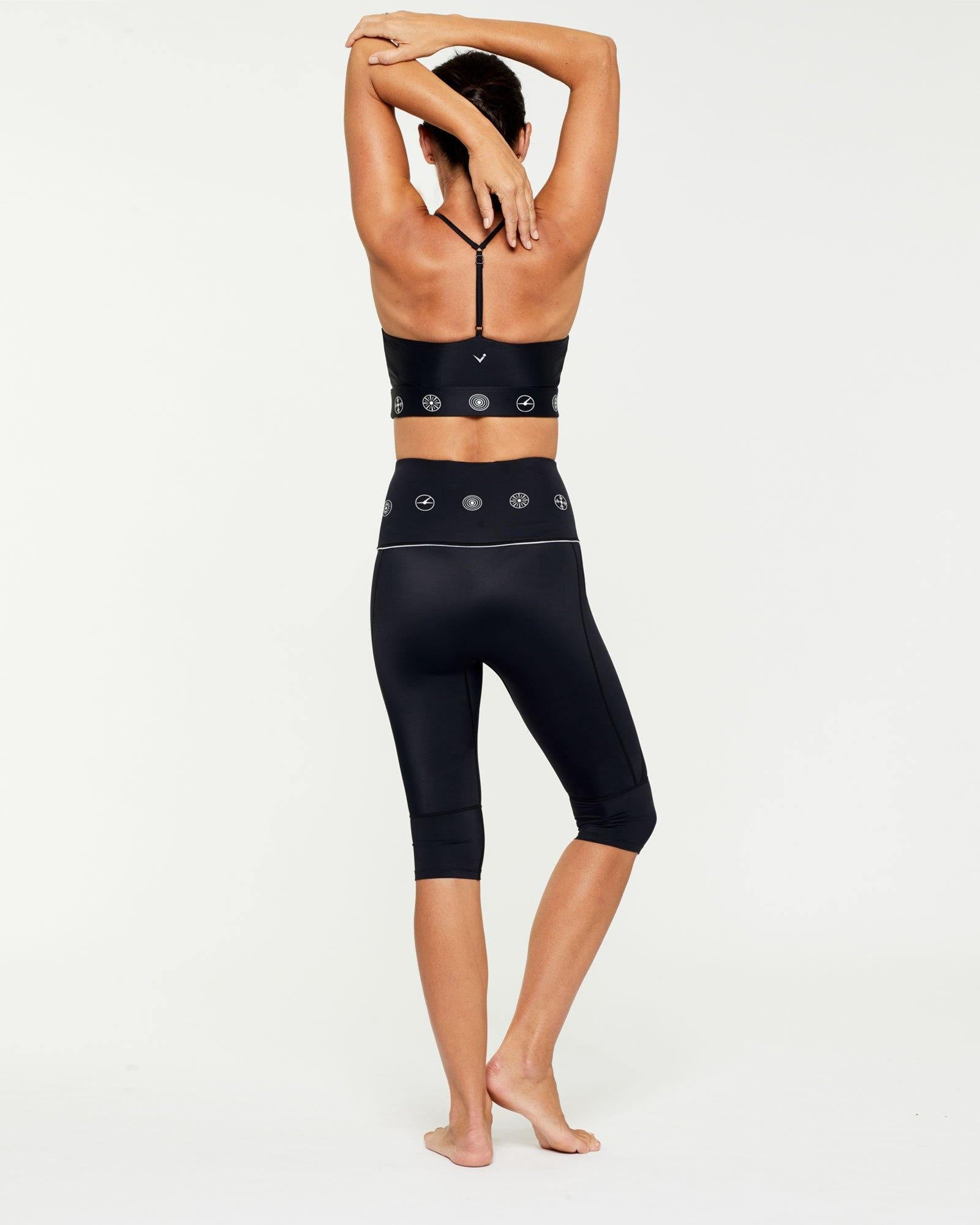 Trapezius Companion crop top high neck finish worn with Sartorius pedal pusher short, black with white symbols, back view