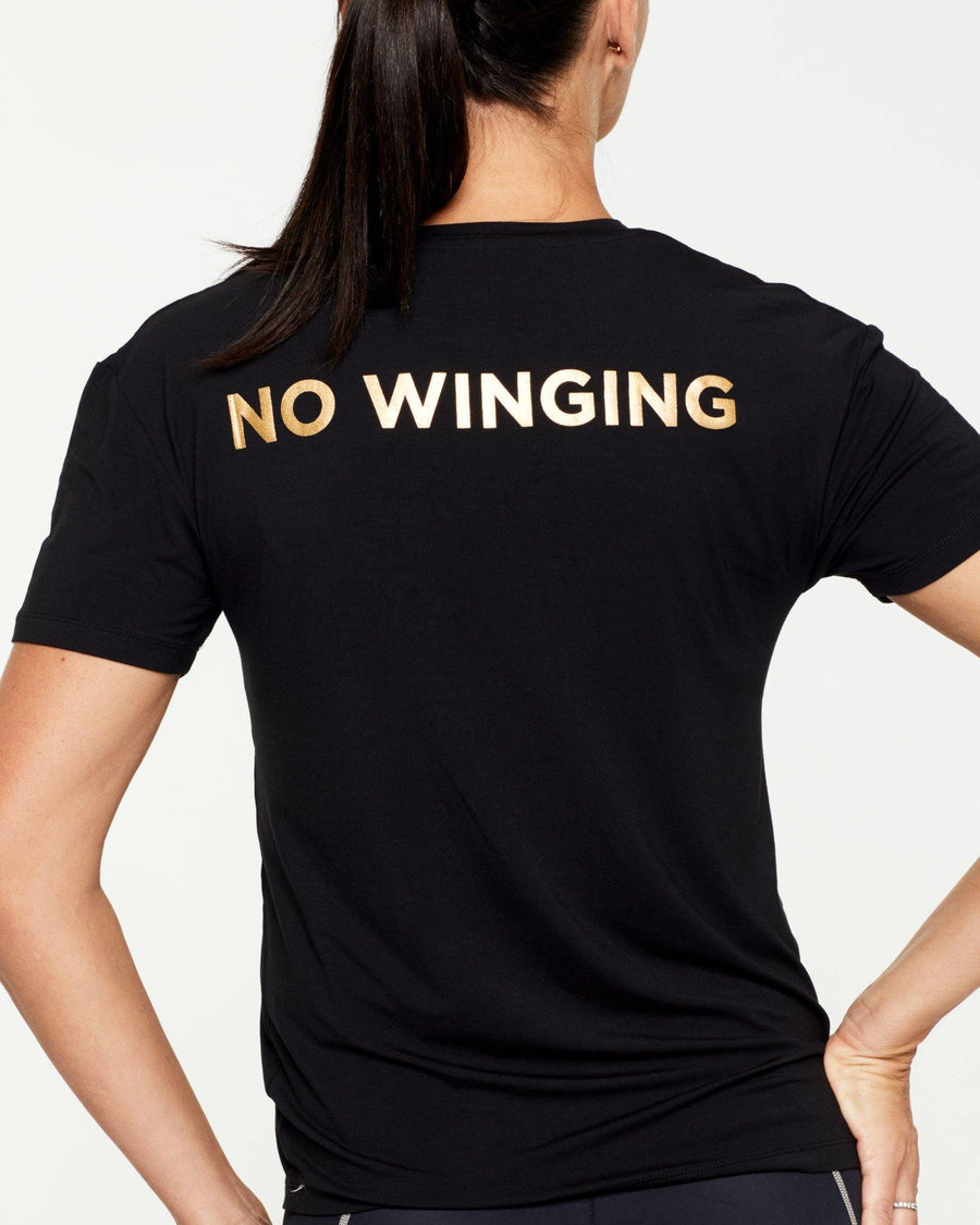 Warrior SCAPULAE T-SHIRT, BLACK WITH METALLIC GOLD MESSAGING, WORN WITH VASTUS LEGGING, FRONT VIEW