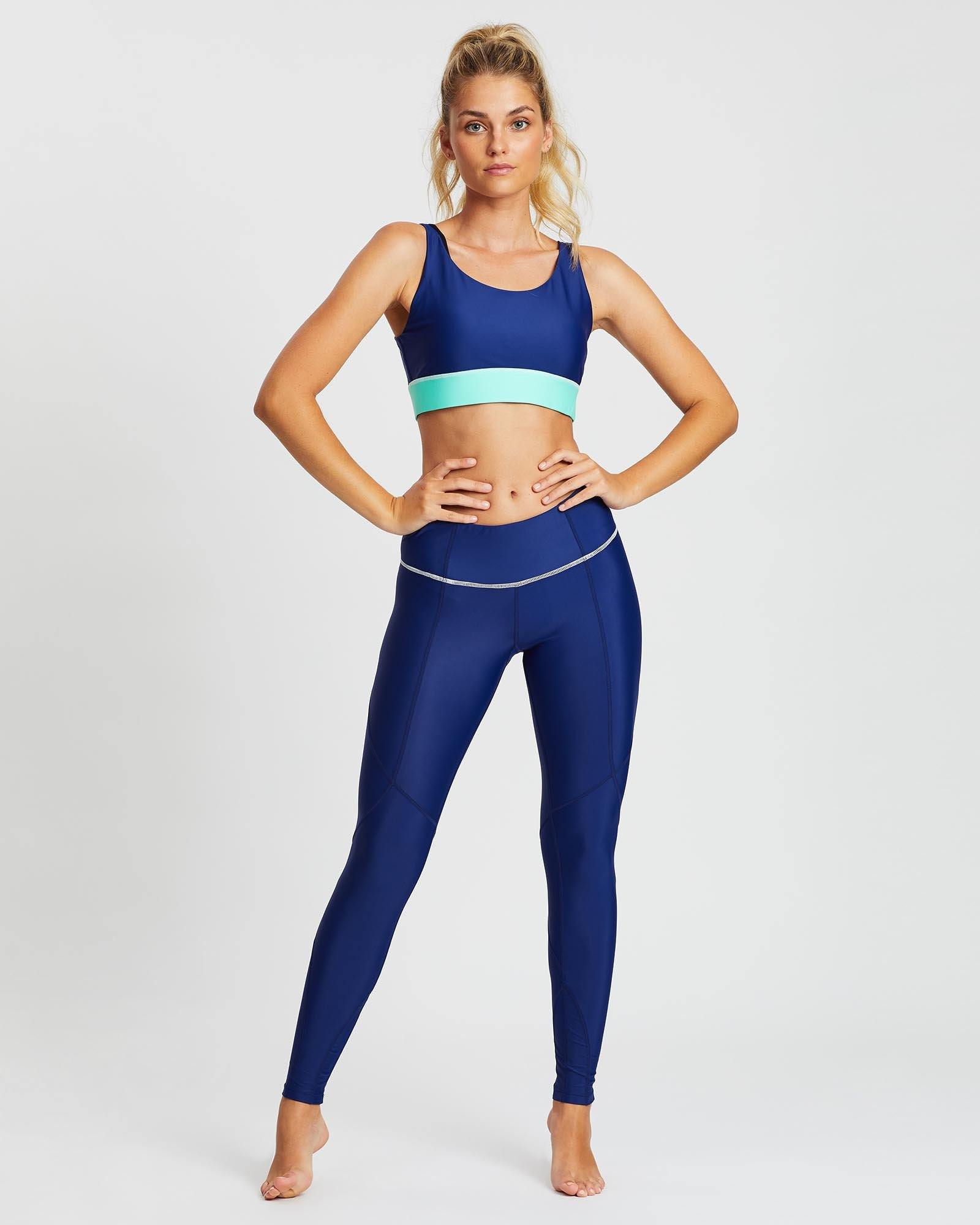 She of the Sea mid waist long Night Blue legging with contrast white stitching between legs and waistband, worn with Pectoralis bra top, front view, for pilates, barre, yoga, gym and studio workouts