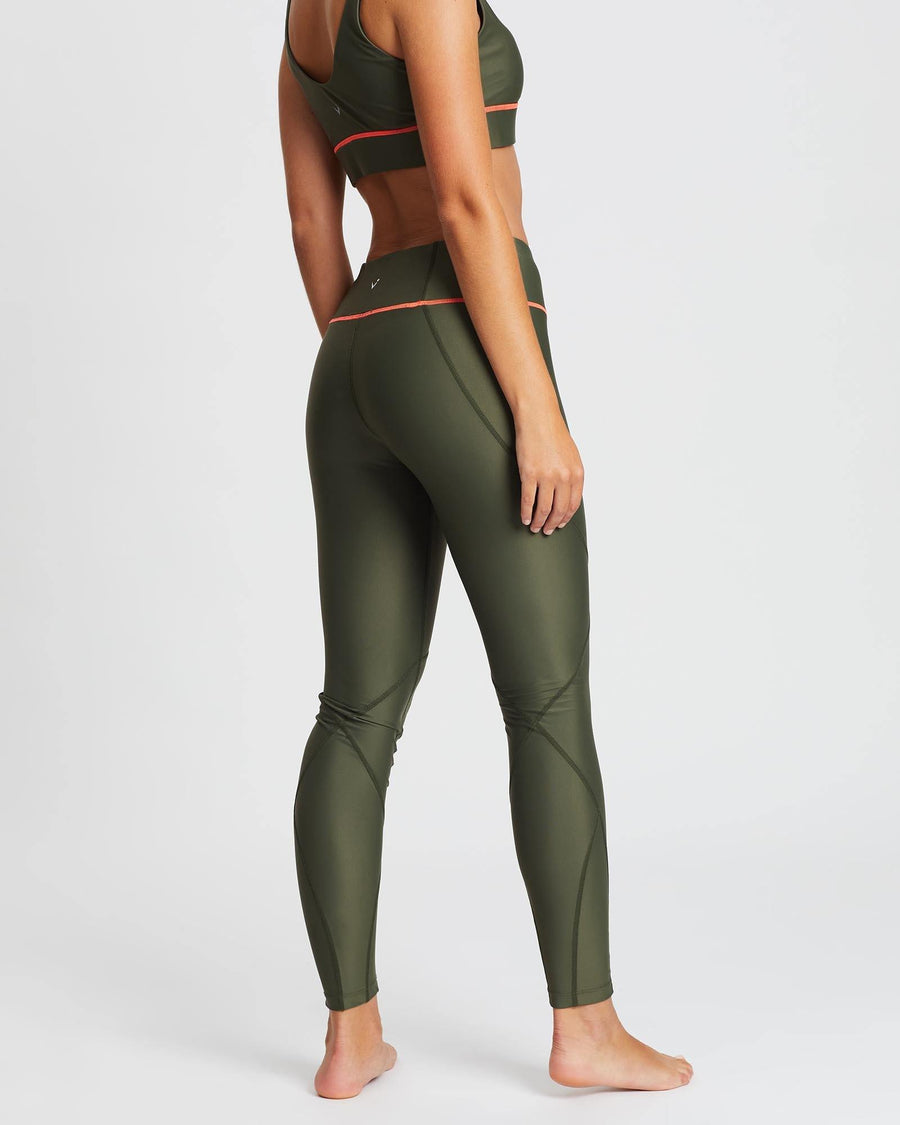 Sergeant Vastus mid waist long army Olive legging with contrast orange stitching between legs and waistband, worn with Pectoralis bra top, front view, for pilates, barre, yoga, gym and studio workouts