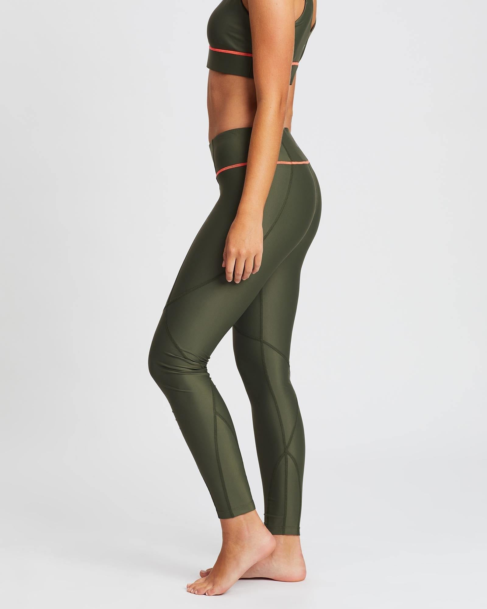 Sergeant Vastus mid waist long army Olive legging with contrast orange stitching between legs and waistband, worn with Pectoralis bra top, side view, for pilates, barre, yoga, gym and studio workouts