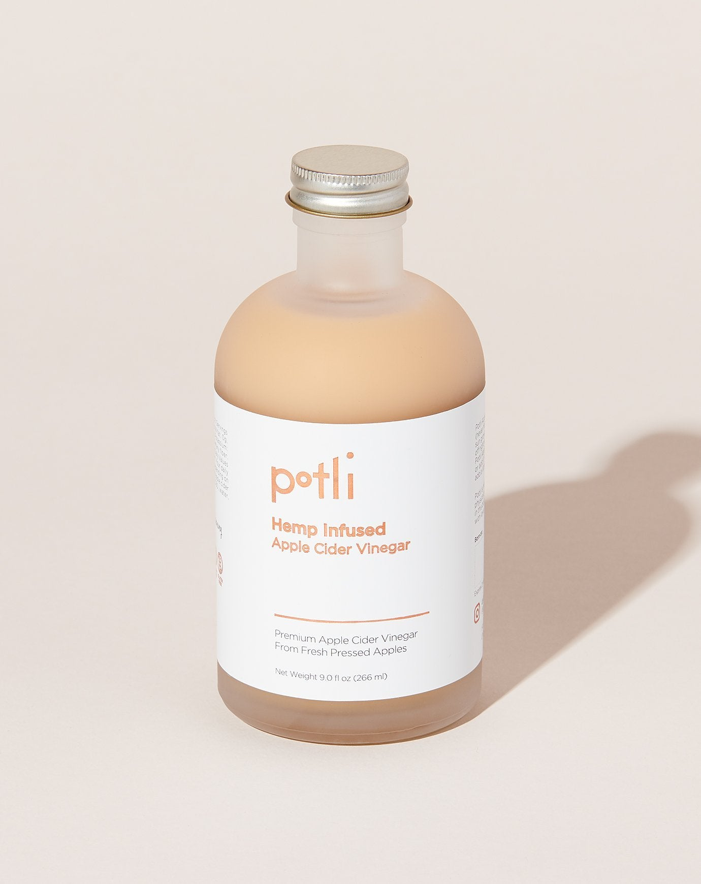 Potli's apple cider vinegar in a 9 oz frosted glass bottle