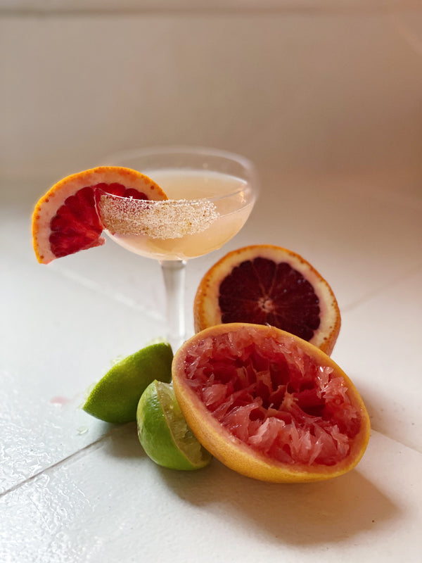 a coup cocktail glass is filled with a peachy liquid and a sugar rim. There is a sliced grapefruit as garnish on the glass and at the base of the glass is 2 squeezed limes, a squeezed grapefruit and half of a blood orange