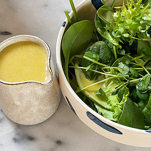 half a bowl of salad is in view and on the other side of it is a pitcher filled with salad dressing. The salad dressing is a bright yellow colour and the salad itself is just green