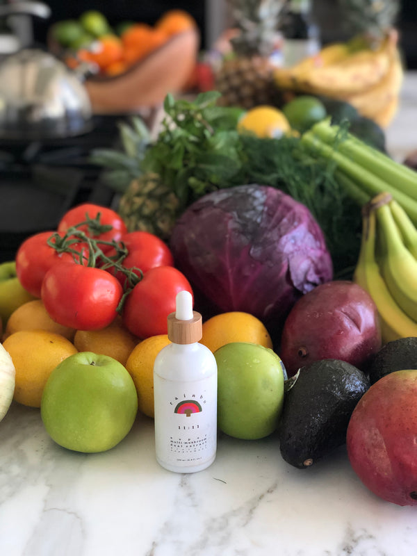 A white dropper bottle of Rainbo medicinal mushroom supplement on a counter filled with fresh colourful produce including apples tomatoes cabbage bananas avocado and greens