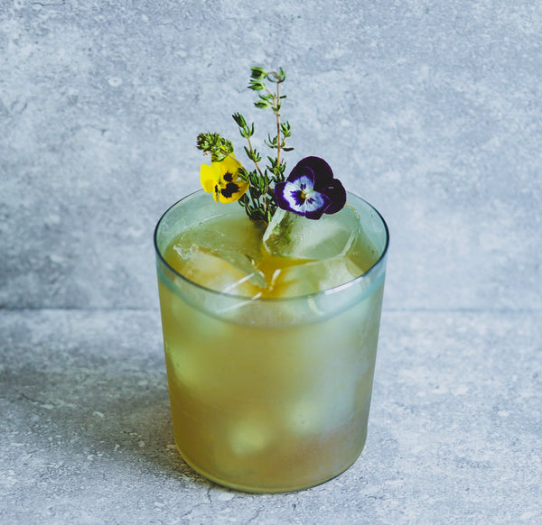 In the centre of a grey marbled background there is a frosted green glass filled with a yellow liquid and ice. It is garnished with two pansy flowers and a sprig of thyme