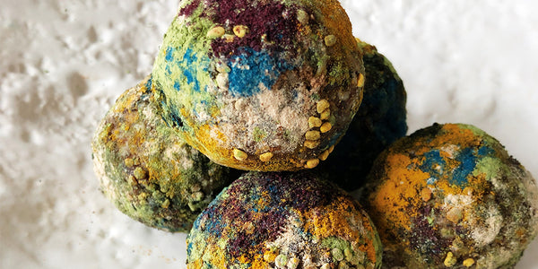 On a textured white plate, there is a close up of five balls stacked onto one another. Each ball has been rolled in various powders such as spirulina, blue majik, tumeric, cinnamon, and bee pollen. Each ball features the colours blue, green, orange