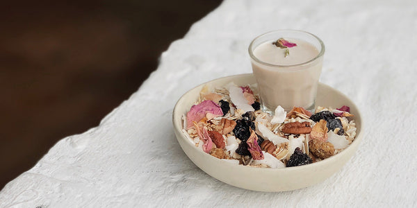 a white bowl sits on a white table with the dark wooden floor in the background. inside the bowl is artisanal granola made with colours pink, brown, white, dark blue pieces. Inside the bowl is also a short clear glass of nut milk made with mushrooms