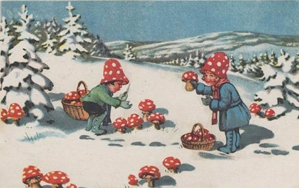 a vintage postcard shows two young children outside in the snow picking bright red mushrooms with white spots on them and putting them in baskets. They wear matching red with white polkadot hats and are surrounded by evergreen trees laden with snow.