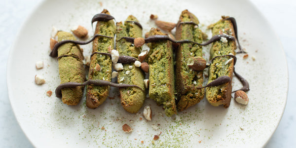 6 chewy matcha biscotti on a plate drizzled with chocolate sauce on top and sprinkled with matcha powder
