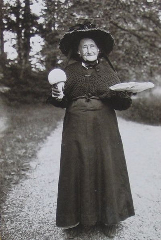 A black and white photograph of an older woman in a black dress with a hat fashioned as a witch hat. She stands in the middle of a road holding two large mushrooms one in each hand.