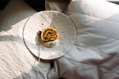 a large white plate sits on top of bedding with a round tan coloured cinnamon roll in the middle and a small golden spoon beside it ready to eat