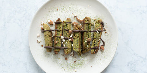 rainbo's chewy matcha biscotti on a plate drizzled with matcha powder and chocolate sauce