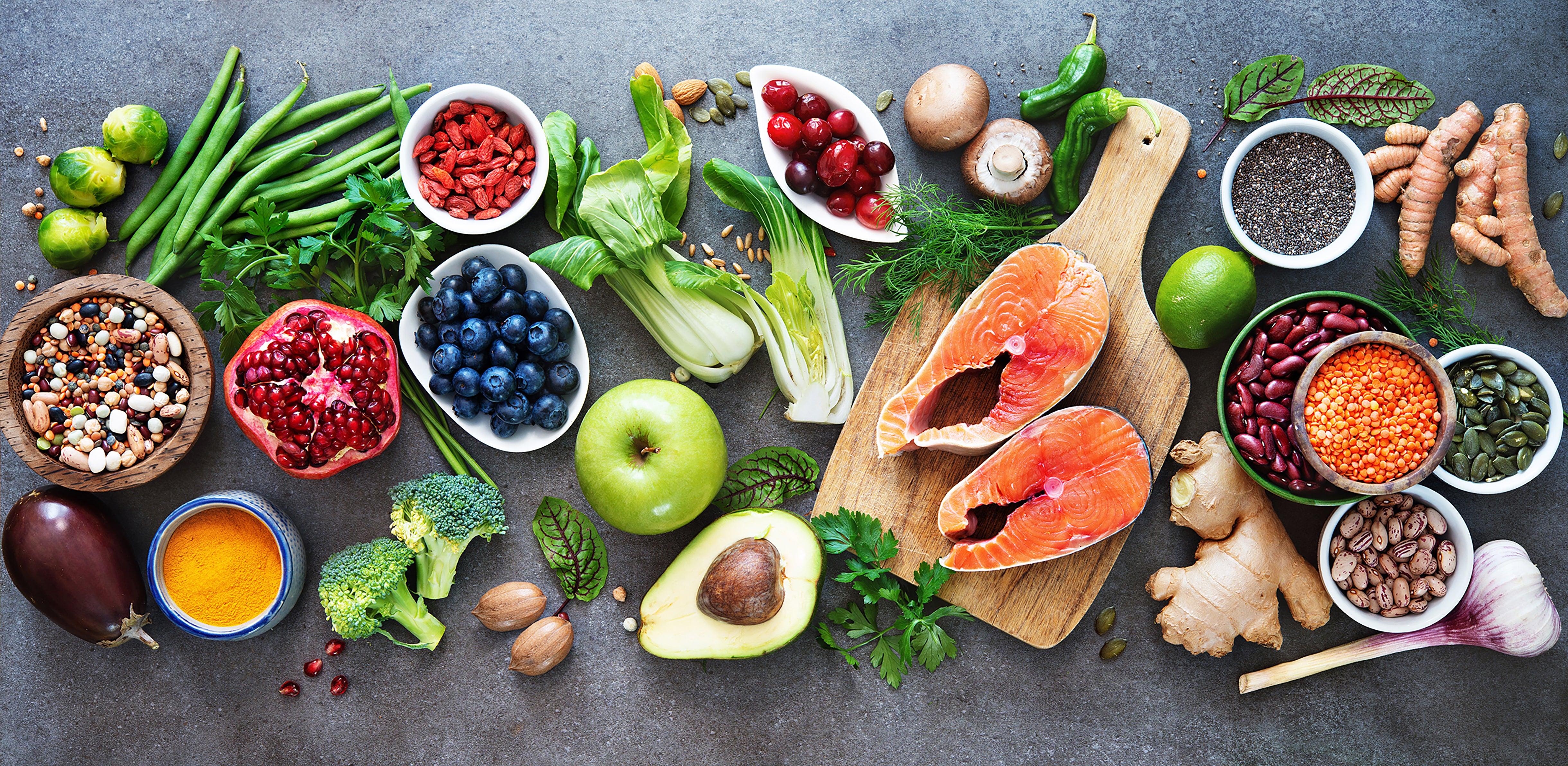 An assorted group of whole foods such as vegetables, fruits, legumes, beans, and salmon on a grey background