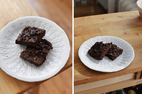 on the left there is a white ceramic plate lightly indented with patterns that has two dark brown brownies with flaked sea salt on top. on the left the same white plate with two dark brown brownies sits on the light coloured wood  kitchen counter