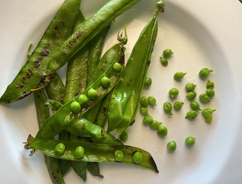some peas and their opened pods on a white plate
