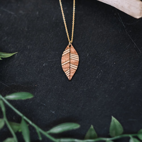 wood leaf necklace with gold accent, gilded wooden necklace, Austin jewelry, artisan wood wearable art, social impact jewelry, ethical accessory