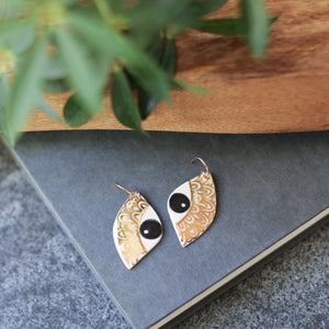 eye with gold brow earrings