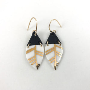 white and gold leaf hanging earrings, gold filigree jewelry, Austin jewelry, porcelain wearable art, social impact jewelry, ethical accessory, black leather earrings