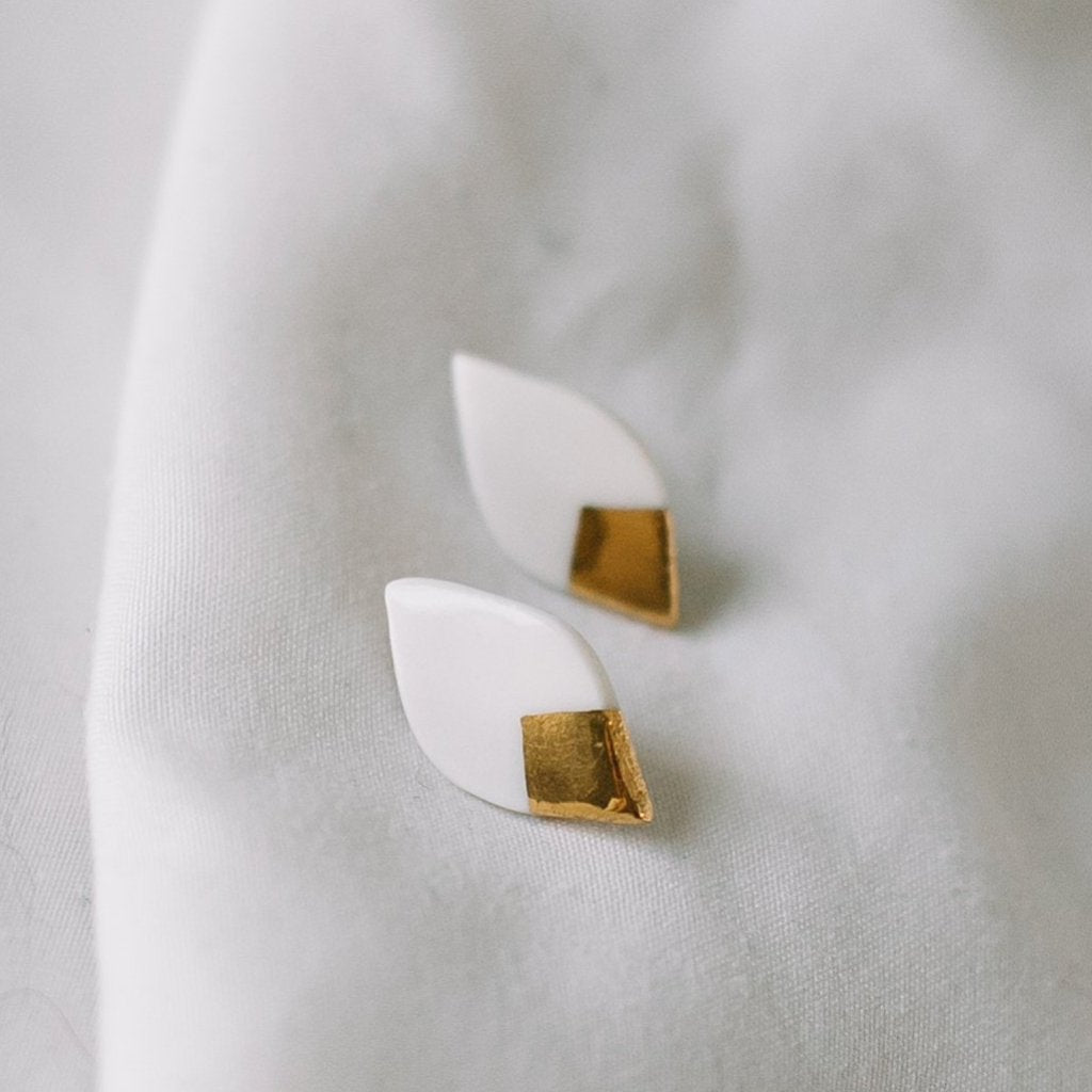 white and gold leaf stud earrings, gold filigree jewelry, Austin jewelry, porcelain wearable art, social impact jewelry, ethical accessory