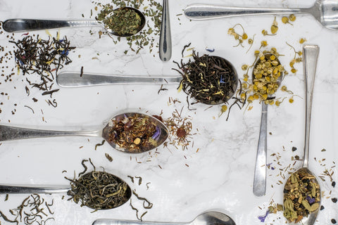 """Several """"deliteacious"""" teas and tisanes with herbs and spices on spoons."""