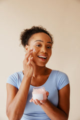 A woman smiles for the camera as she sits and practices her skincare routine, rubbing skin treatment onto her face.