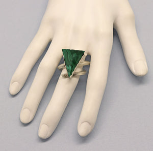 triangle shaped beveled gemstone ring shown on a hand