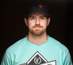 Head shot of Cassidy. Black hat and teal shirt