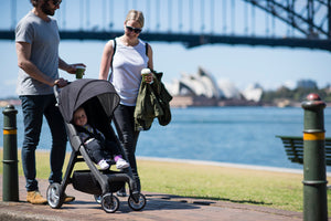 Lightweight Chit Chat stroller. Great for travel stroller. Stroller made from recyclable materials. Image: Larktale family strolls in a park with their black frame chit chat stroller.