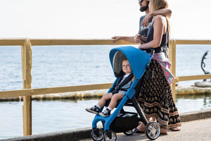 Blue Frame Stroller. Compact folding stroller. Chit Chat Stroller. Image: child sits in a Larktale chit chat stroller with a blue frame