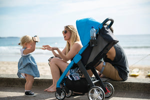 Lightweight Blue Frame Stroller, weights 14.5 lbs! Chit Chat stroller. Image: Family sits by the ocean with the blue framed chit chat stroller in freshwater blue