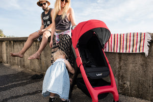 Red Frame stroller. Chit Chat stroller. Recyclable stroller. Lightweight stroller. Image: Larktale family sits at the beach with the chit chat stroller in barossa red