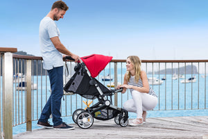 Larktale coast stroller. small folding stroller. stroller for newborn. travel system ready. best stroller for city families. family strolls along the ocean with their coast stroller in red.