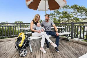 Coast stroller. Compact folding stroller. Small Fold stroller. Yellow Stroller. Easy to travel stroller. Image: Larktale family sits outside with the compact folded coast stroller