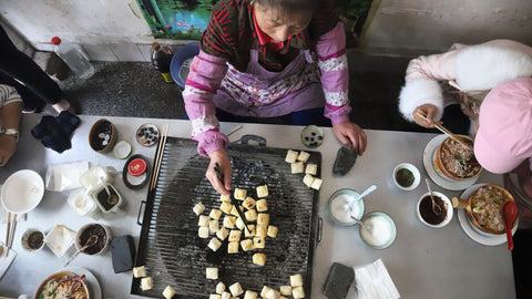 Eating grilled tofu in Yuan Yang province, South China