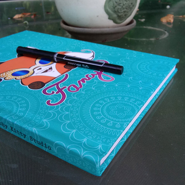 "Angled photo of journal on glass patio table. There is a pen resting on top of the journal, a flower pot in the background. The journal is teal blue with a mandala pattern in white. There's a cute marshmallow fox wearing wing-shaped rhinestone sunglasses with blue lenses on the front.  ""Fancy"" is written in script underneath the fox."