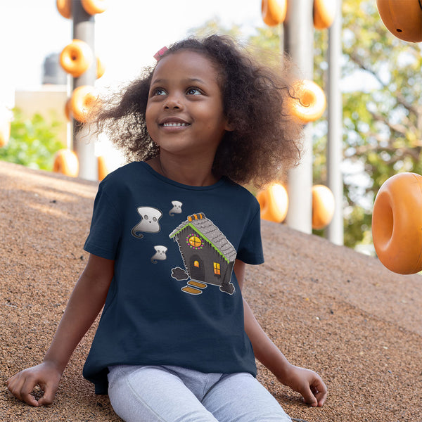 young black girl wearing Ghost and Haunted Gingerbread House kids' tee in Navy. There's a black gingerbread house with gray roof, orange and black  gummies on the roof, and three marshmallow ghosts floating to the left of the house.
