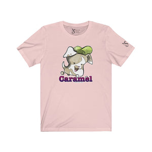 "Light pink Caramel marshmallow puppy tee. Marshmallow puppy is white with tan markings and a green hat, which is flying off her head. Her name, ""Caramel"" is written in bold font, and is colored red-purple gradient."